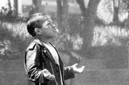 Niño de Guatemala bajo la lluvia
